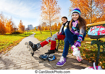 Kids putting on roller blades - 10 and 11 years old couple...