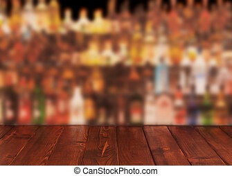 Dark wooden table against interior of bar with alcohol...