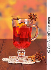 Glass of mulled wine on napkin on wooden table
