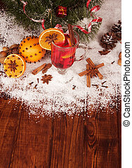 Glass of mulled wine and orange on a snowy table - Snow,...