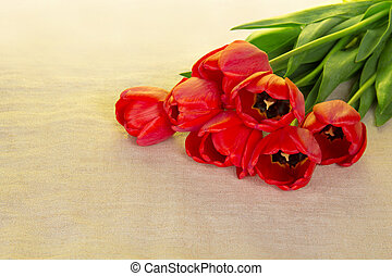 Bouquet of red tulips on a sackcloth
