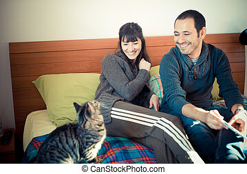 couple in love on the bed using tablet at home