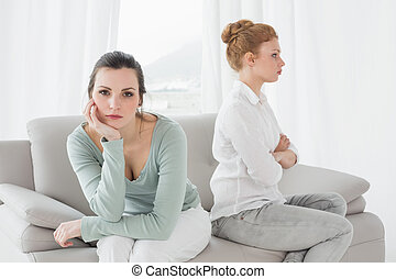 Unhappy friends not talking after argument on the couch -...