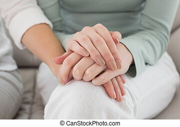 Close-up mid section of female friends touching hands at...