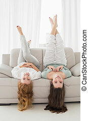 Portrait of two smiling young female friends lying on sofa...