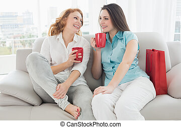 Female friends with coffee cups - Two happy young female...