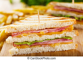club sandwich with french fries on wooden table