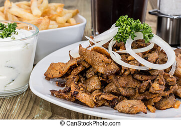 Heap of Kebab meat on a plate on wooden background