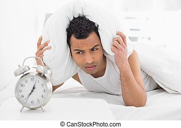 Man covering ears with pillow as he looks at alarm clock in...