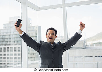 Elegant young businessman cheering in office - Cheerful...