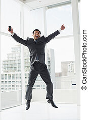 Cheerful elegant young businessman cheering in office - Full...