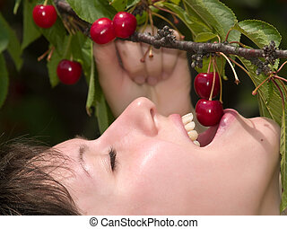 Cherry tasting - Beautiful young lady eats red cherry just...