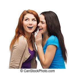 two smiling girls whispering gossip - friendship, happiness...