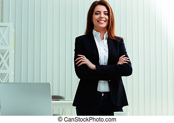 Young pensive businesswoman standing with arms folded at...