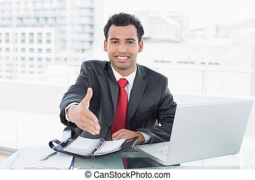 Businessman offering a handshake at office desk - Portrait...