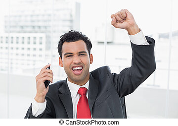 Businessman cheering with clenched fist at office - Portrait...