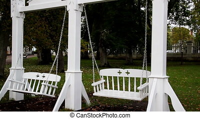 Two bench swing attached to its pillar and is painted in...