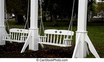 Two white bench swing at the park where you can also see big...