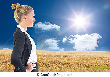 Composite image of businesswoman standing with hands on hips...