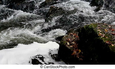 Water flowing on top of big rocks on the stream that is...