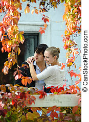 A young couple embraces in the garden