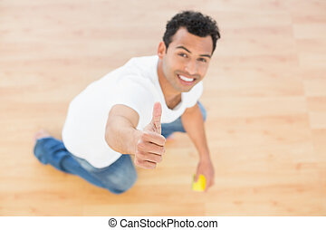 Smiling man cleaning the floor while gesturing thumbs up -...