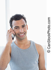Portrait of a young smiling man using mobile phone
