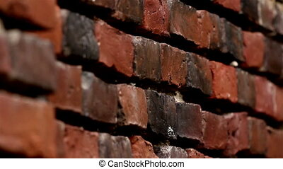 Some Old red bricks on the wall are darkened