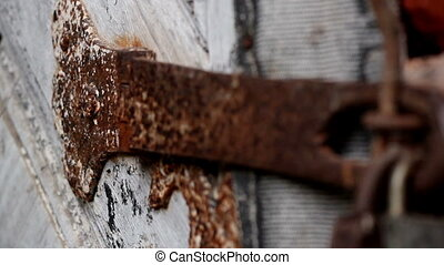 Up close of the rusty padlock used to bolt the door