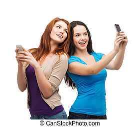 two smiling teenagers with smartphones - technology,...