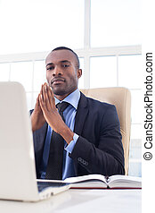 Confident in his power. Confident young African businessman keeping his hands clasped and looking at camera while sitting at his working place