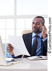 Businessman at work. Confident young African businessman...