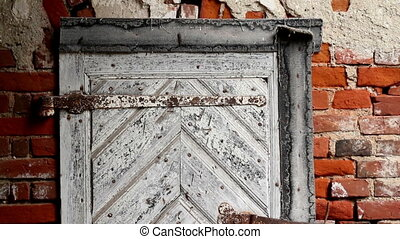 White door bolted with a rusty padlock to make sure that...