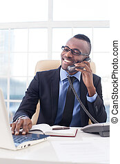 Businessman at work. Confident young African businessman in glasses talking on the mobile phone and using computer while sitting at his working place
