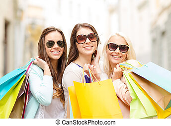 three smiling girls with shopping bags in city - shopping,...