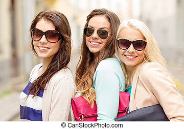 three smiling women in sunglasses with bags