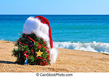 Christmas tree and santa hat on the sand in the beach...