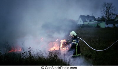 Firemen extinguishing fire that has broke out in the open...