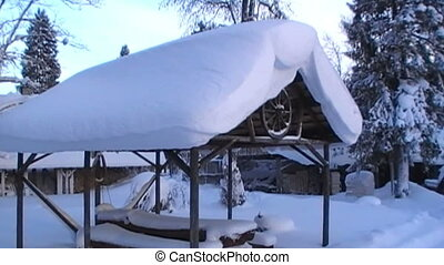 Roof of the shed is covered in a lot of snow