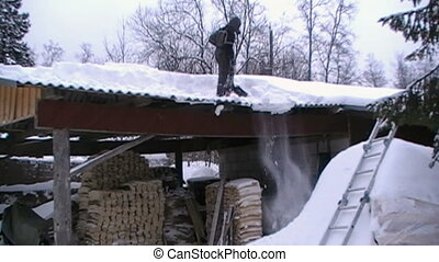 Person getting snow out of the roof