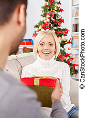 Is it for me? Cheerful young woman sitting on the couch and receiving a gift box from her boyfriend sitting close to her