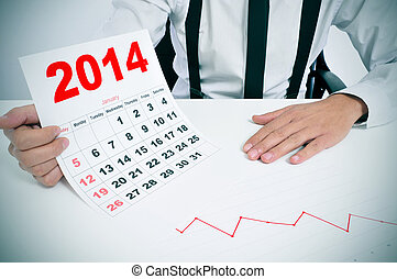 man in suit with a chart and a 2014 calendar