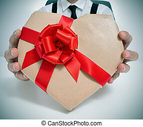 heart-shaped gift - man wearing a suit sitting in a table...