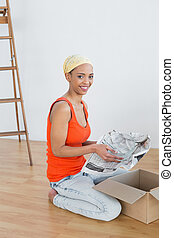 Happy young woman unwrapping boxes - Side view portrait of a...