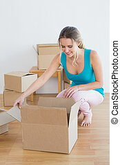 Woman unwrapping boxes in new house - Happy young woman...