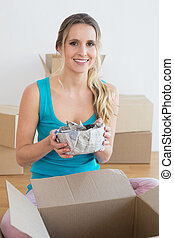 Woman unwrapping boxes in new house - Portrait of a happy...