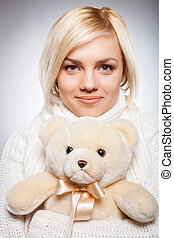 Girl with Teddy bear Beautiful young blond hair woman...