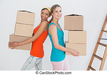 Female friends moving together in a new house - Side view...