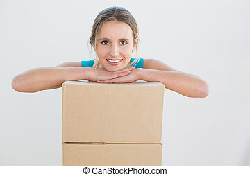 Portrait of a young woman with a stack of boxes