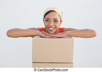 Portrait of a smiling young woman with boxes